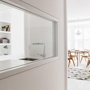 Offene, Kleine Shabby-Style Küche ohne Insel in U-Form mit flächenbündigen Schrankfronten, weißen Schränken, Quarzit-Arbeitsplatte, Küchenrückwand in Weiß, Küchengeräten aus Edelstahl, hellem Holzboden und Unterbauwaschbecken in London