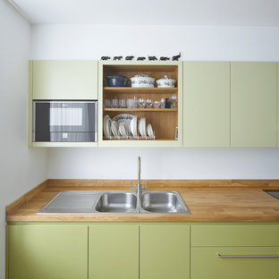 Photo of a medium sized contemporary single-wall kitchen in London with a double-bowl sink, flat-panel cabinets, green cabinets, wood worktops and no island.