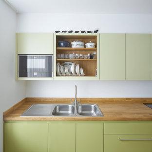 ロンドンの中サイズのコンテンポラリースタイルのおしゃれなI型キッチン (ダブルシンク、フラットパネル扉のキャビネット、緑のキャビネット、木材カウンター、アイランドなし) の写真
