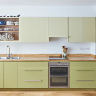 Inspiration for a mid-sized eclectic single-wall open plan kitchen in London with a double-bowl sink, flat-panel cabinets, green cabinets, wood benchtops, panelled appliances, light hardwood floors and no island.