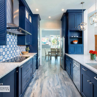 Design ideas for a mid-sized beach style galley eat-in kitchen in Tampa with an undermount sink, shaker cabinets, blue cabinets, quartz benchtops, multi-coloured splashback, ceramic splashback, stainless steel appliances, ceramic floors, a peninsula, grey floor and white benchtop.