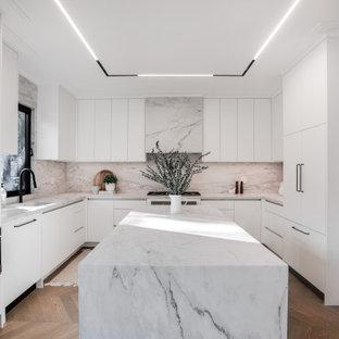 トロントの中くらいのトランジショナルスタイルのおしゃれなキッチン (アンダーカウンターシンク、フラットパネル扉のキャビネット、白いキャビネット、タイルカウンター、白いキッチンパネル、磁器タイルのキッチンパネル、パネルと同色の調理設備、無垢フローリング、茶色い床、白いキッチンカウンター) の写真