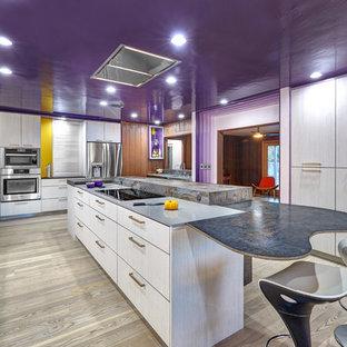 Cette photo montre une grande cuisine moderne en L fermée avec un évier encastré, un placard à porte plane, des portes de placard violettes, un plan de travail en quartz modifié, une crédence blanche, une crédence en carreau de porcelaine, un électroménager en acier inoxydable, un sol en bois clair et un îlot central.