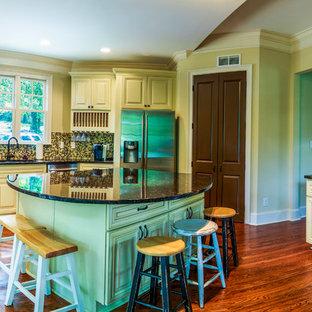 アトランタの広いトラディショナルスタイルのおしゃれなキッチン (アンダーカウンターシンク、レイズドパネル扉のキャビネット、白いキャビネット、御影石カウンター、マルチカラーのキッチンパネル、モザイクタイルのキッチンパネル、シルバーの調理設備、淡色無垢フローリング、茶色い床) の写真