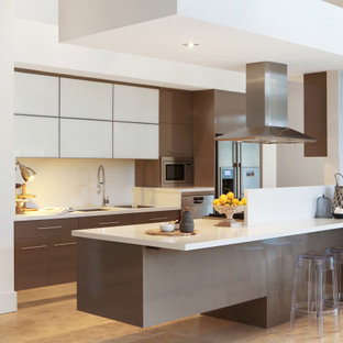 This is an example of a contemporary galley kitchen in Central Coast with an undermount sink, flat-panel cabinets, brown cabinets, stainless steel appliances, with island, beige floor and white benchtop.