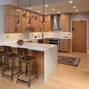 シカゴのインダストリアルスタイルのおしゃれなキッチン (エプロンフロントシンク、フラットパネル扉のキャビネット、中間色木目調キャビネット、グレーのキッチンパネル、シルバーの調理設備、淡色無垢フローリング、ベージュの床、白いキッチンカウンター) の写真