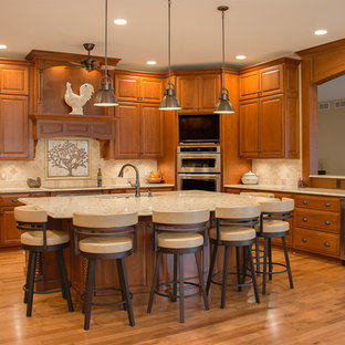 Große Klassische Wohnküche in U-Form mit Unterbauwaschbecken, profilierten Schrankfronten, hellbraunen Holzschränken, Küchengeräten aus Edelstahl, hellem Holzboden, Kücheninsel, Quarzwerkstein-Arbeitsplatte, Küchenrückwand in Beige und Rückwand aus Steinfliesen in Minneapolis