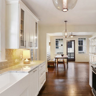 Small transitional eat-in kitchen designs - Eat-in kitchen - small transitional dark wood floor eat-in kitchen idea in New Orleans with a farmhouse sink, shaker cabinets, white cabinets, marble countertops, green backsplash, glass tile backsplash, stainless steel appliances and no island