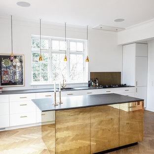 Неиссякаемый источник вдохновения для домашнего уюта: большая параллельная кухня в современном стиле с обеденным столом, накладной раковиной, плоскими фасадами, белыми фасадами, гранитной столешницей, фартуком цвета металлик, светлым паркетным полом, островом и фартуком из стекла