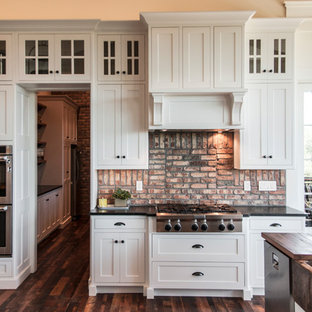 Huge traditional open concept kitchen designs - Inspiration for a huge timeless l-shaped dark wood floor open concept kitchen remodel in Other with an undermount sink, raised-panel cabinets, white cabinets, onyx countertops, red backsplash, brick backsplash, stainless steel appliances and an island