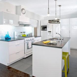 Trendy gray floor kitchen photo in New York with mosaic tile backsplash, white appliances, a single-bowl sink, flat-panel cabinets, white cabinets, metallic backsplash and granite countertops