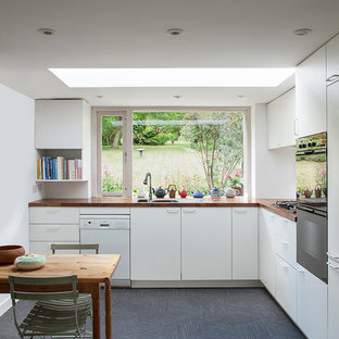 Design ideas for a mid-sized contemporary l-shaped eat-in kitchen in London with a double-bowl sink, flat-panel cabinets, white cabinets, wood benchtops, white splashback, stainless steel appliances, vinyl floors and grey floor.