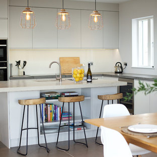Design ideas for a medium sized contemporary galley kitchen/diner in Channel Islands with flat-panel cabinets, grey cabinets, concrete worktops, beige splashback, glass sheet splashback, ceramic flooring, an island, grey floors, a submerged sink, black appliances and grey worktops.