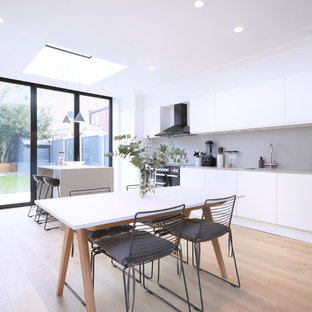 Contemporary single-wall kitchen/diner in London with a submerged sink, flat-panel cabinets, white cabinets, beige splashback, black appliances, light hardwood flooring, an island, beige floors and beige worktops.