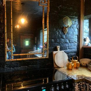 Geschlossene, Kleine Rustikale Küche in U-Form mit Küchenrückwand in Schwarz, schwarzen Elektrogeräten, Backsteinboden und rotem Boden in Sussex