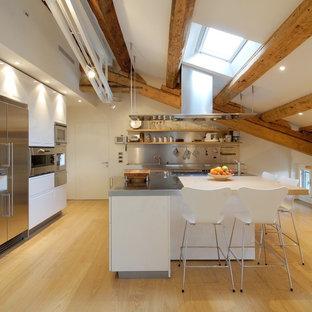 Inredning av ett modernt stort linjärt kök och matrum, med en köksö, stänkskydd med metallisk yta, stänkskydd i metallkakel, släta luckor, vita skåp, bänkskiva i rostfritt stål, rostfria vitvaror och ljust trägolv