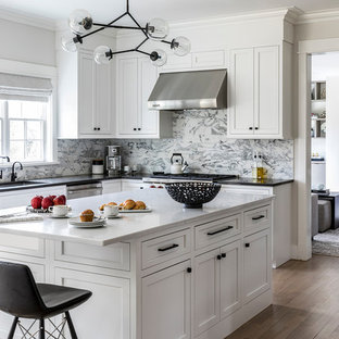 Mid-sized contemporary eat-in kitchen photos - Mid-sized trendy u-shaped light wood floor eat-in kitchen photo in New York with recessed-panel cabinets, white cabinets, quartz countertops, marble backsplash, stainless steel appliances and an island