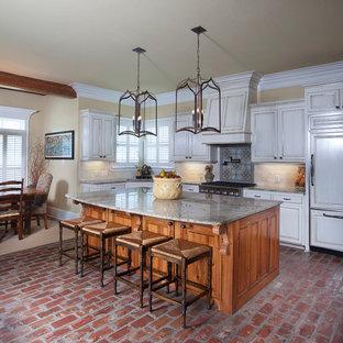Foto di una cucina abitabile chic con ante con bugna sagomata, ante bianche, paraspruzzi beige, elettrodomestici da incasso, pavimento in mattoni, isola e paraspruzzi in travertino