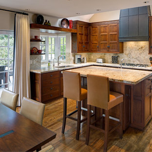 Large transitional eat-in kitchen pictures - Large transitional l-shaped medium tone wood floor eat-in kitchen photo in Other with an undermount sink, raised-panel cabinets, medium tone wood cabinets, granite countertops, stone slab backsplash, stainless steel appliances, an island and beige countertops