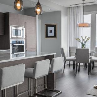 Esempio di una cucina minimal di medie dimensioni con lavello sottopiano, ante lisce, ante marroni, top in marmo, paraspruzzi blu, elettrodomestici in acciaio inossidabile, parquet scuro, isola, pavimento marrone e paraspruzzi con lastra di vetro