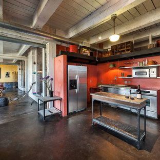 Industrial kitchen inspiration - Urban l-shaped concrete floor kitchen photo in Portland with stainless steel appliances, an island, stainless steel cabinets, an undermount sink and red backsplash