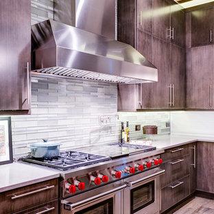 Große, Offene Klassische Küche in U-Form mit Unterbauwaschbecken, flächenbündigen Schrankfronten, grauen Schränken, Quarzwerkstein-Arbeitsplatte, Küchenrückwand in Grün, Rückwand aus Glasfliesen, Küchengeräten aus Edelstahl, braunem Holzboden und Kücheninsel in Chicago