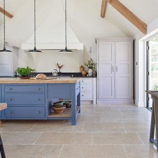 ウィルトシャーのカントリー風おしゃれなキッチン (ライムストーンの床、フラットパネル扉のキャビネット、白いキャビネット) の写真