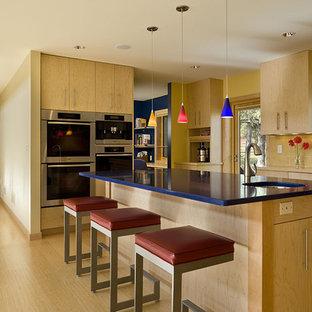 Moderne Küche mit Küchengeräten aus Edelstahl, flächenbündigen Schrankfronten, hellen Holzschränken und blauer Arbeitsplatte in Minneapolis