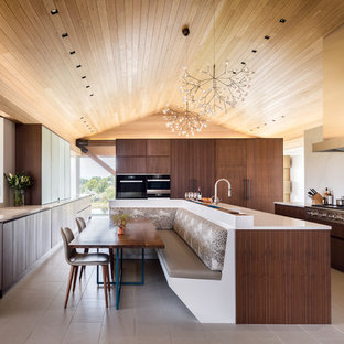 Expansive contemporary u-shaped eat-in kitchen in Other with flat-panel cabinets, dark wood cabinets, marble splashback, stainless steel appliances, ceramic floors, with island, an undermount sink, marble benchtops, white splashback and beige floor.