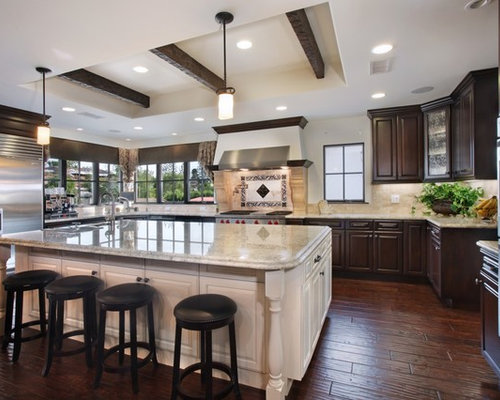 Tuscan Kitchen Photo In Orange County With Raised Panel Cabinets, Stainless  Steel Appliances And