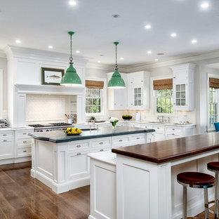 Inspiration för ett vintage l-kök, med en undermonterad diskho, skåp i shakerstil, vita skåp, vitt stänkskydd, stänkskydd i keramik, rostfria vitvaror, mellanmörkt trägolv, flera köksöar och träbänkskiva