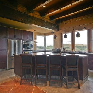 カルガリーの中サイズのサンタフェスタイルのおしゃれなキッチン (アンダーカウンターシンク、シェーカースタイル扉のキャビネット、濃色木目調キャビネット、御影石カウンター、シルバーの調理設備の、コンクリートの床、グレーの床) の写真