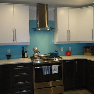 バンクーバーの広いビーチスタイルのおしゃれなキッチン (ドロップインシンク、フラットパネル扉のキャビネット、グレーのキャビネット、ラミネートカウンター、青いキッチンパネル、ガラス板のキッチンパネル、シルバーの調理設備、セラミックタイルの床) の写真