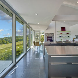 Design ideas for a large modern l-shaped eat-in kitchen in Philadelphia with a double-bowl sink, flat-panel cabinets, stainless steel cabinets, stainless steel benchtops, stainless steel appliances, ceramic floors, multiple islands and black floor.