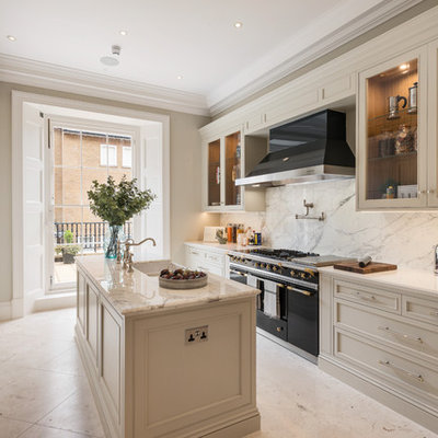 Mid-sized elegant galley marble floor and white floor kitchen photo in London with marble countertops, white backsplash, marble backsplash, an island, white countertops, a farmhouse sink, recessed-panel cabinets, white cabinets and black appliances