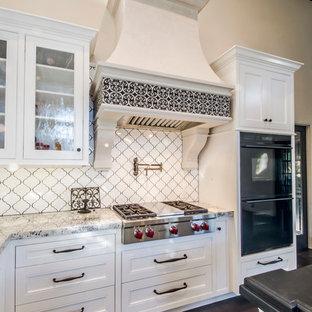 Offene, Geräumige Mediterrane Küche in L-Form mit weißen Schränken, Granit-Arbeitsplatte, Küchenrückwand in Weiß, Rückwand aus Keramikfliesen, schwarzen Elektrogeräten, dunklem Holzboden, Kücheninsel und Kassettenfronten in Santa Barbara