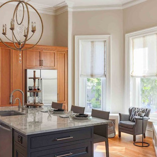Traditional kitchen designs - Elegant medium tone wood floor and orange floor kitchen photo in Boston with an undermount sink, shaker cabinets, medium tone wood cabinets, stainless steel appliances and an island