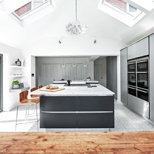 This is an example of a large contemporary single-wall eat-in kitchen in Wiltshire with a farmhouse sink, flat-panel cabinets, grey cabinets, marble benchtops, stainless steel appliances, ceramic floors and multiple islands.