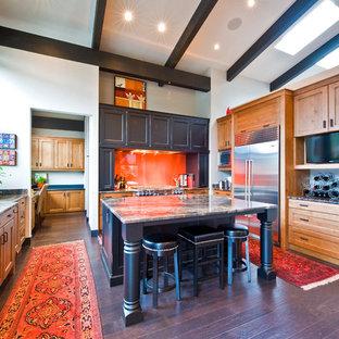 Klassische Küche in U-Form mit hellbraunen Holzschränken, Küchenrückwand in Orange und Küchengeräten aus Edelstahl in Calgary