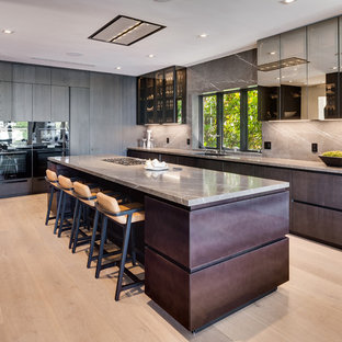 Large contemporary kitchen ideas - Inspiration for a large contemporary light wood floor and beige floor kitchen remodel in Miami with flat-panel cabinets, gray backsplash, stone slab backsplash, black appliances, an island, a single-bowl sink, brown cabinets and gray countertops