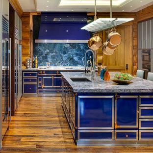 Ejemplo de cocina rural, grande, con fregadero bajoencimera, armarios con paneles lisos, encimera de granito, suelo de madera en tonos medios, una isla, puertas de armario grises, salpicadero azul, electrodomésticos de colores y encimeras azules