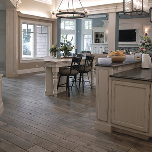 Huge coastal eat-in kitchen ideas - Example of a huge beach style u-shaped medium tone wood floor, brown floor and vaulted ceiling eat-in kitchen design in Chicago with an undermount sink, beaded inset cabinets, white cabinets, granite countertops, multicolored backsplash, ceramic backsplash, two islands and black countertops
