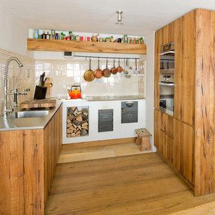 Urige Küche in U-Form mit integriertem Waschbecken, flächenbündigen Schrankfronten, Schränken im Used-Look, Edelstahl-Arbeitsplatte und Küchenrückwand in Beige in Sonstige
