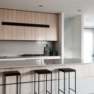 Ejemplo de cocina comedor lineal, contemporánea, de tamaño medio, con fregadero bajoencimera, armarios con paneles lisos, puertas de armario de madera clara, encimera de acrílico, salpicadero beige, salpicadero de vidrio templado, suelo de terrazo, una isla, suelo gris y encimeras beige