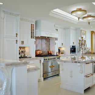 Cette image montre une cuisine ouverte victorienne en U avec un placard avec porte à panneau encastré, des portes de placard blanches, une crédence beige, une crédence en dalle de pierre, un îlot central, un sol beige et un plan de travail beige.