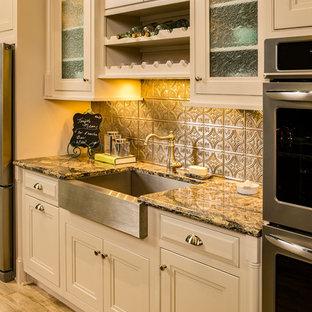 Esempio di una cucina parallela classica chiusa e di medie dimensioni con lavello stile country, ante con bugna sagomata, ante beige, top in granito, paraspruzzi a effetto metallico, paraspruzzi con piastrelle di metallo, elettrodomestici in acciaio inossidabile, pavimento in travertino e isola