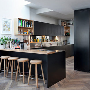 Design ideas for a mid-sized contemporary l-shaped eat-in kitchen in Dublin with an integrated sink, flat-panel cabinets, stainless steel benchtops, metallic splashback, medium hardwood floors, a peninsula and black cabinets.