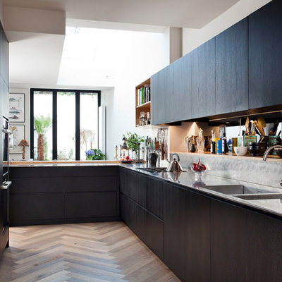 Kitchen - mid-sized contemporary l-shaped medium tone wood floor kitchen idea in Dublin with an integrated sink, flat-panel cabinets, stainless steel countertops, metallic backsplash, a peninsula and black cabinets