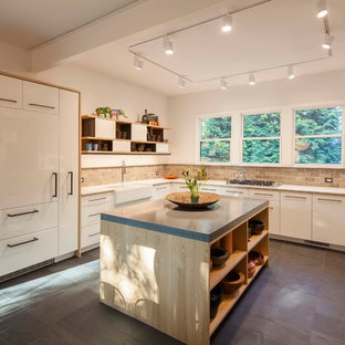 Photo of a modern u-shaped eat-in kitchen in Boston with an integrated sink, flat-panel cabinets, white cabinets, concrete benchtops, beige splashback, mosaic tile splashback, white appliances, with island, black floor, white benchtop and slate floors.