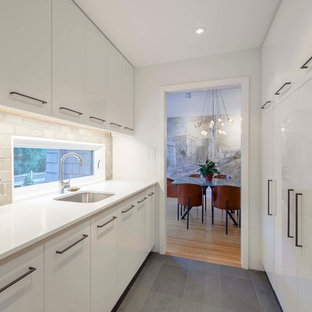 Contemporary galley kitchen in Boston with an undermount sink, flat-panel cabinets, white cabinets, grey splashback, concrete benchtops, white appliances, black floor, yellow benchtop and slate floors.